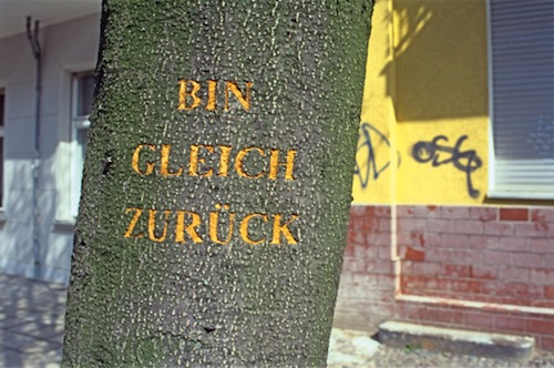 Vor dem Haus, in dem ich wohne, steht ein Baum. Bevor ich Berlin verlasse, schneide ich »Bin gleich zurück« in die Rinde des Baumes. <em>There is a tree in front of my house. Before I leave Berlin, I cut »Back soon« in the bark of the tree.</em>